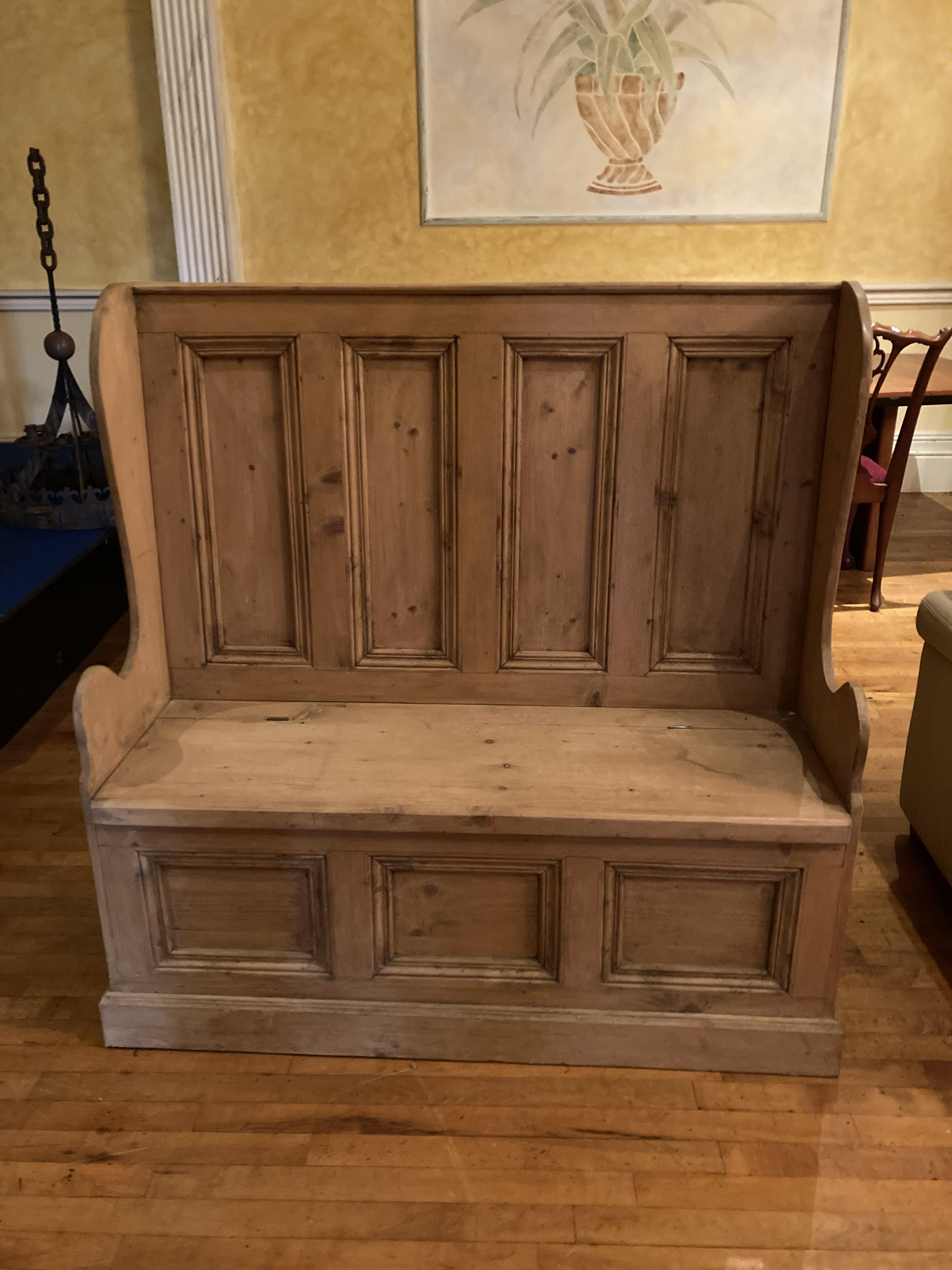 A Victorianstyle wing back pine Settle Bench, with a four panel back above a lift up seat and three