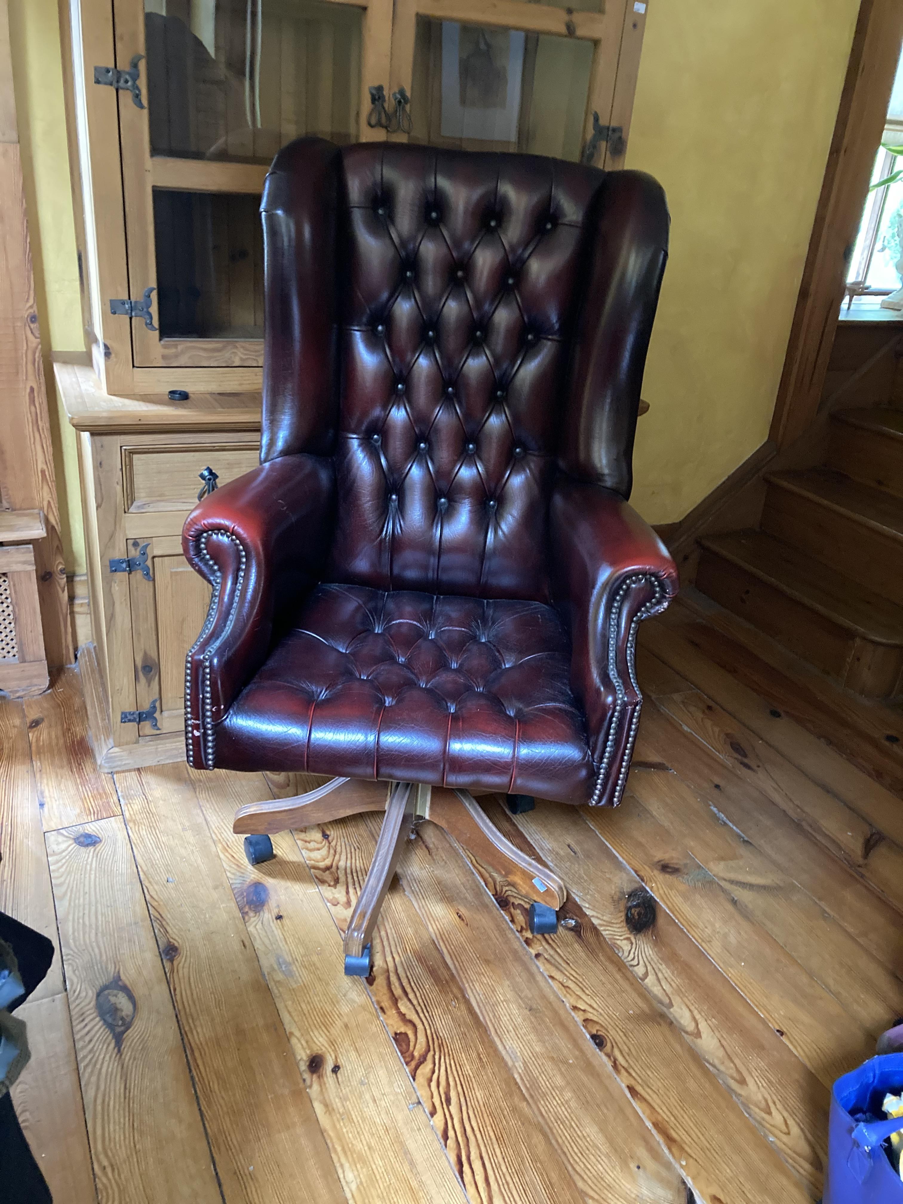 A leather Georgian style high back swivel Armchair, covered in red deep button hide. (1)