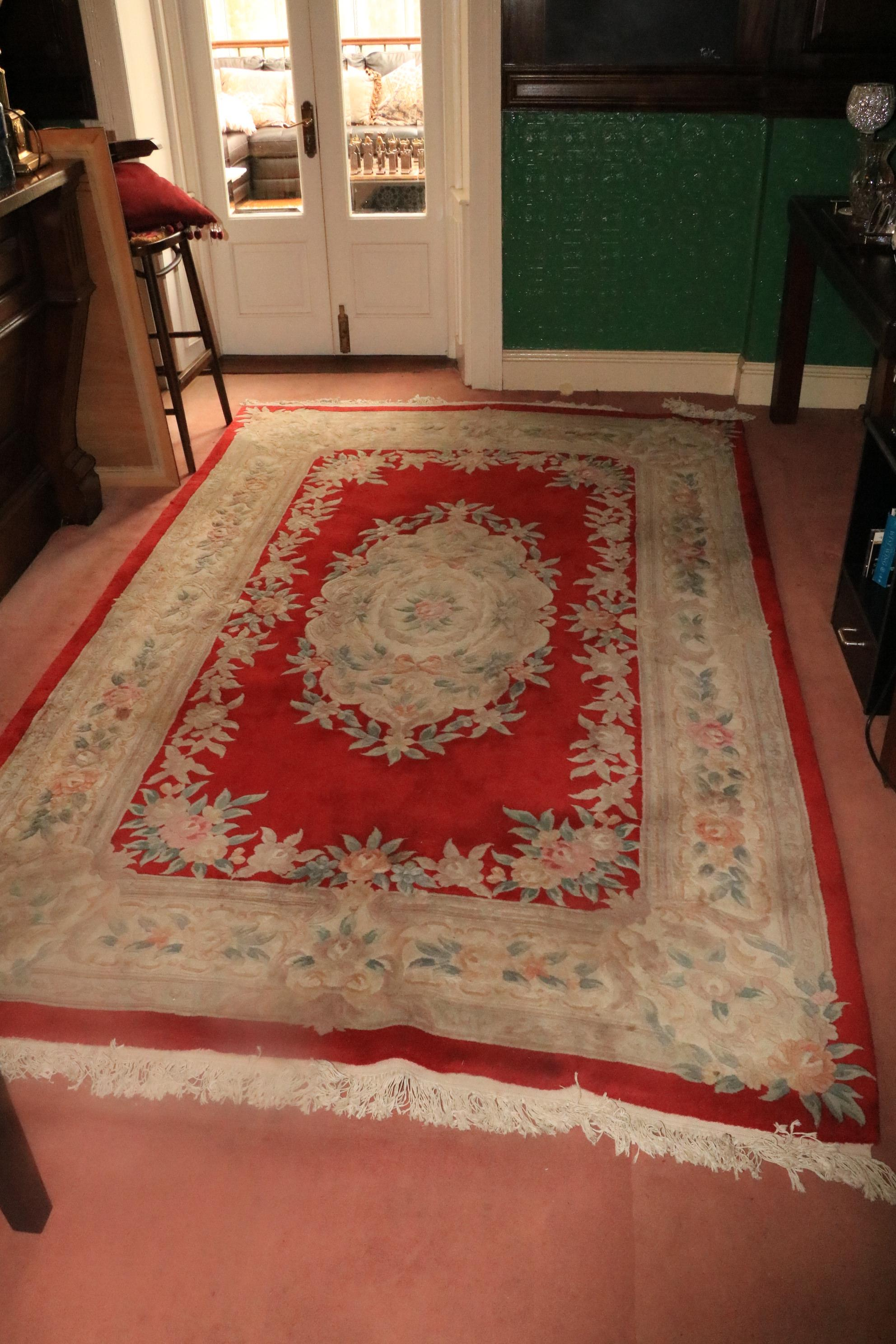 A heavy Chinese Rug, the centre red ground surrounded by a large floral border and similar decorated