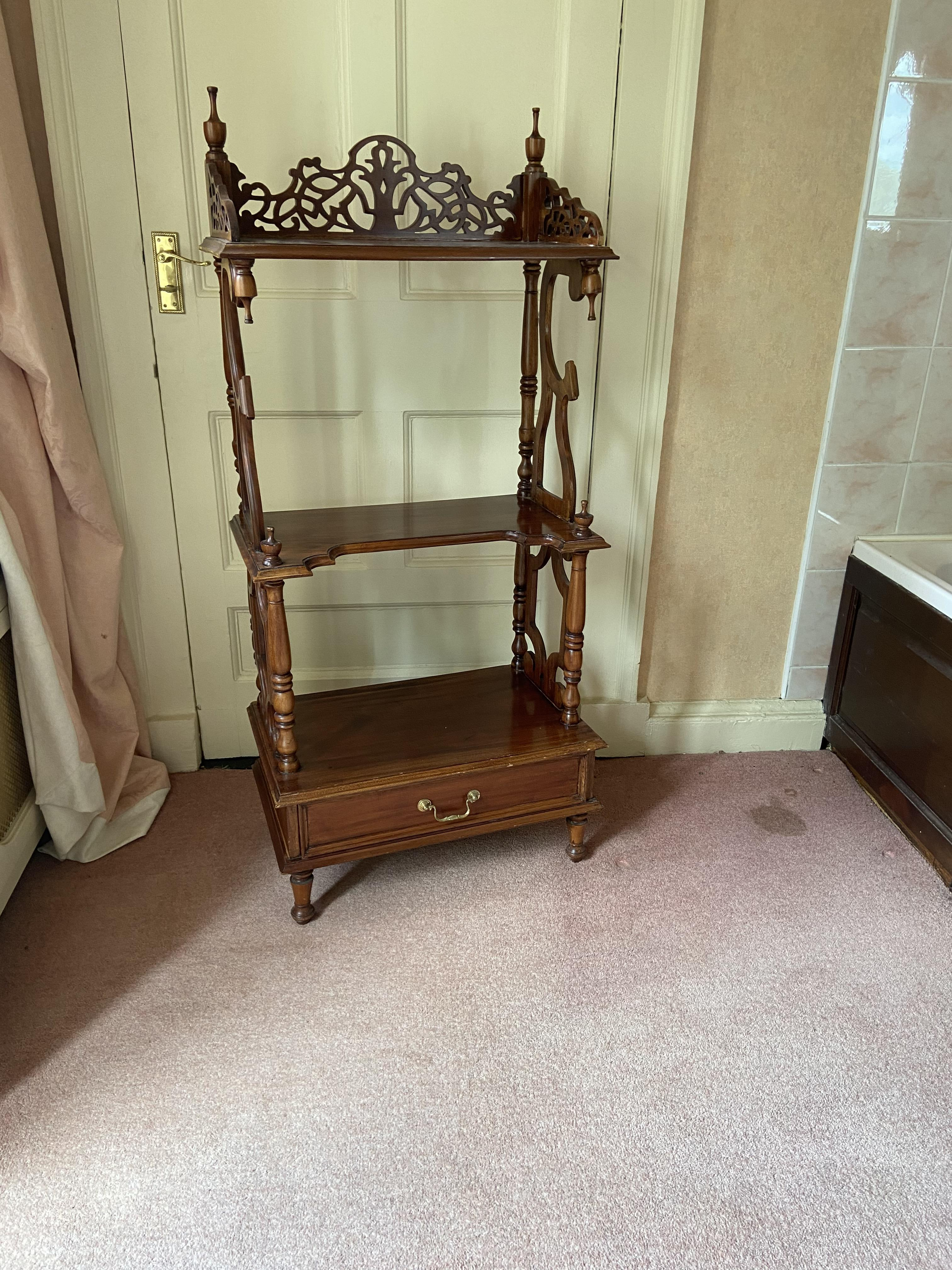 A three tier mahogany Whatnot, with three-quarter openwork gallery with base drawer on turned