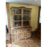 A pine Kitchen Cupboard, with arched top, glazed doors, on a base with drawers and presses,