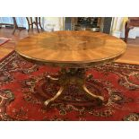 A Victorian oval inlaid walnut Loo Table, on four fluted and turned stems on a quadruple pod with