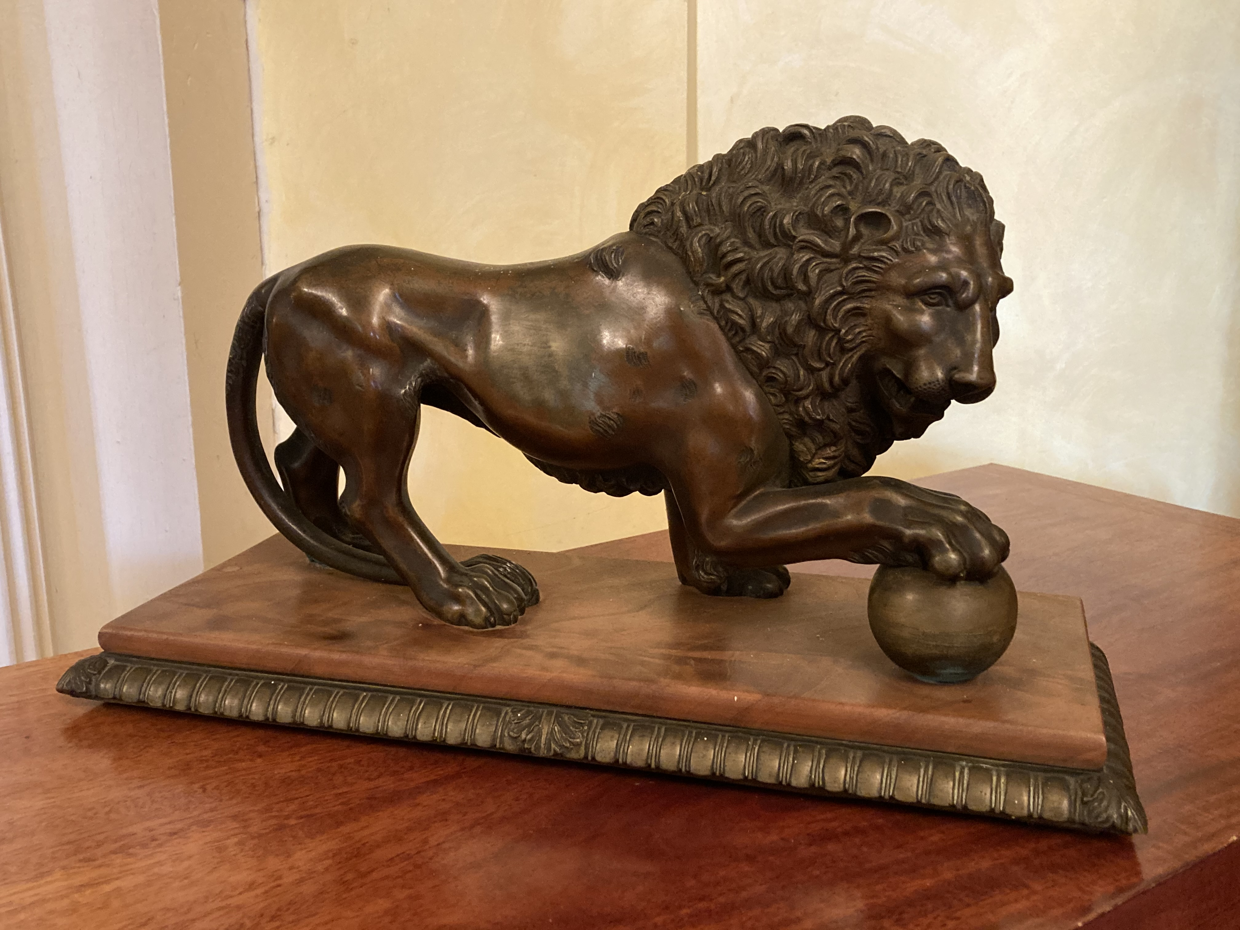 A bronze Figure of a Medici Lion, with right front paw on a sphere, on bronze and wooden base,
