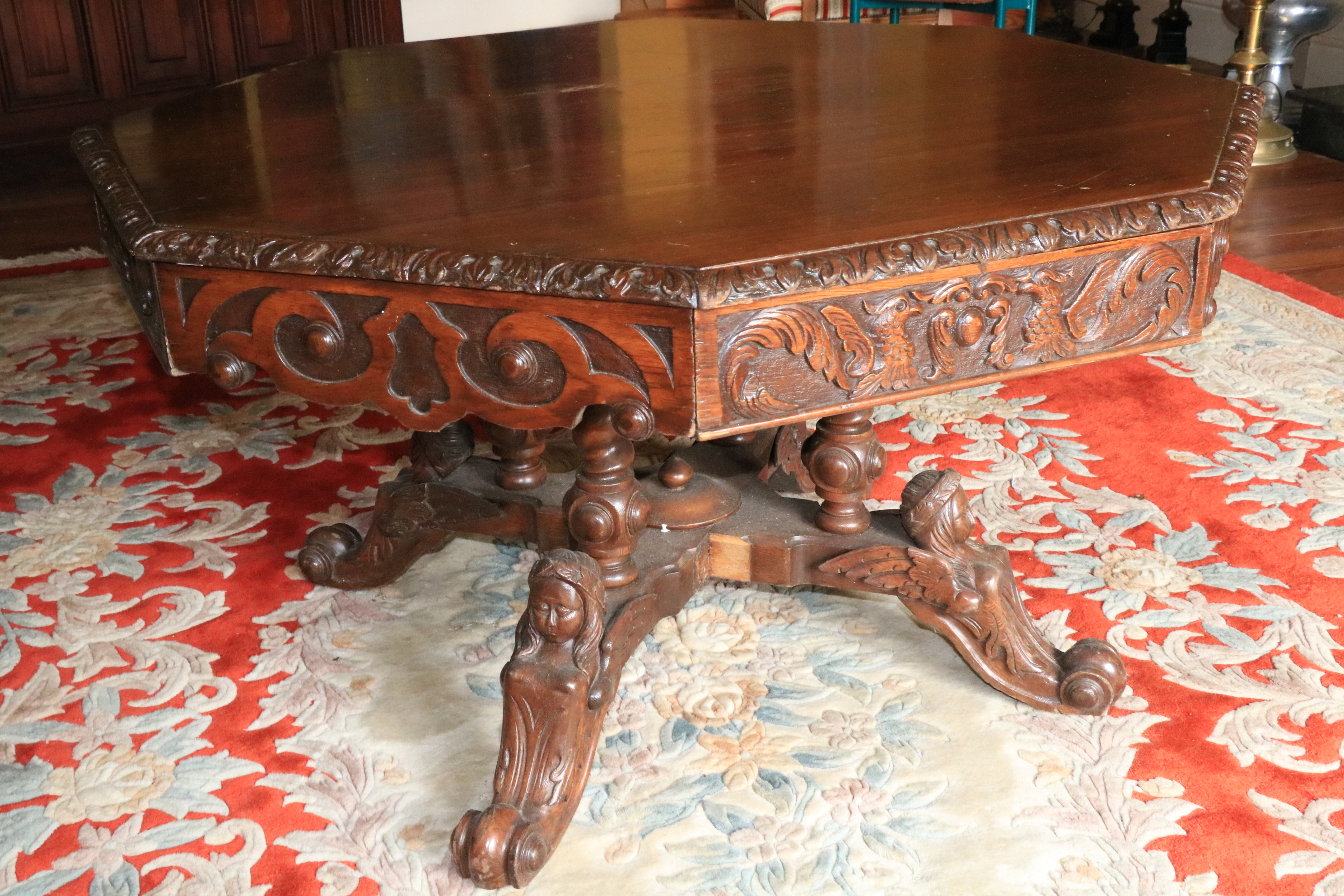 A Victorian carved oak Library Drum Table, with octagonal top above four mock and four frieze