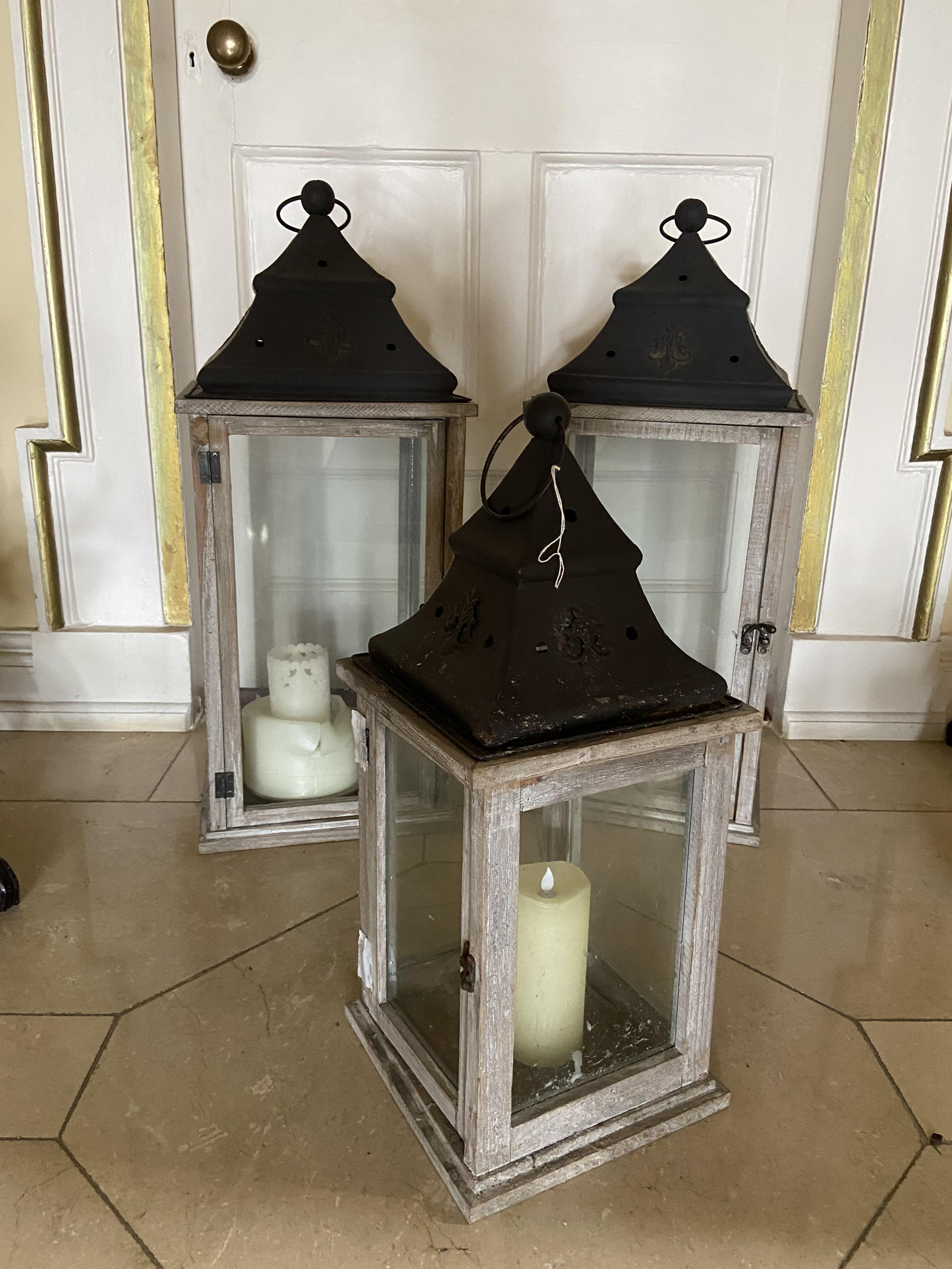 A pair of large square wooden Lanterns, each with four glazed panels and a metal roof with ring