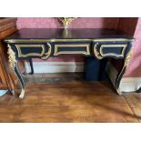 An ebonised and parcel gilt French style Centre Table, with serpentine shaped moulded top on