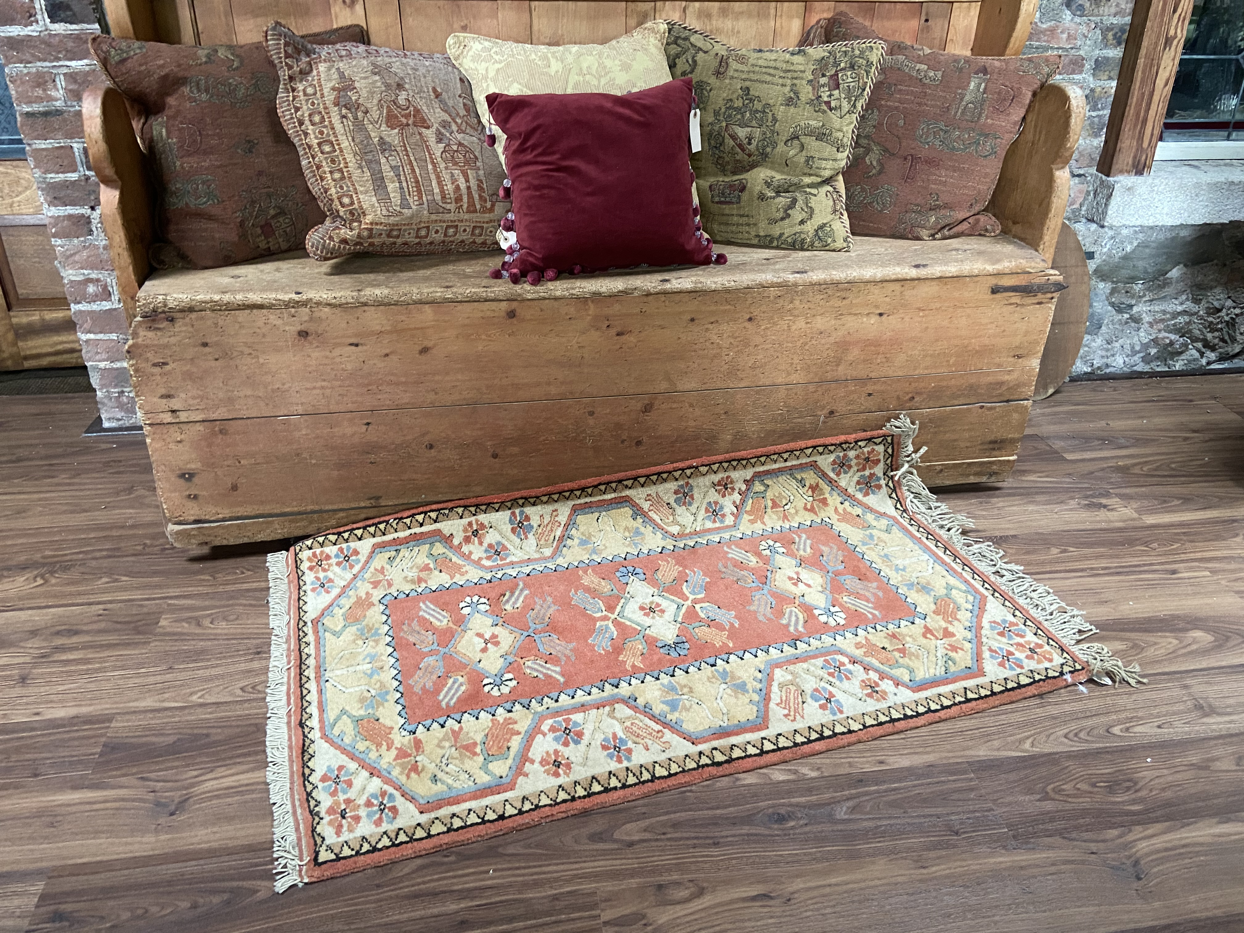A small Turkish Rug, the iron red ground with three medallions inside an ivory border, 59'' x