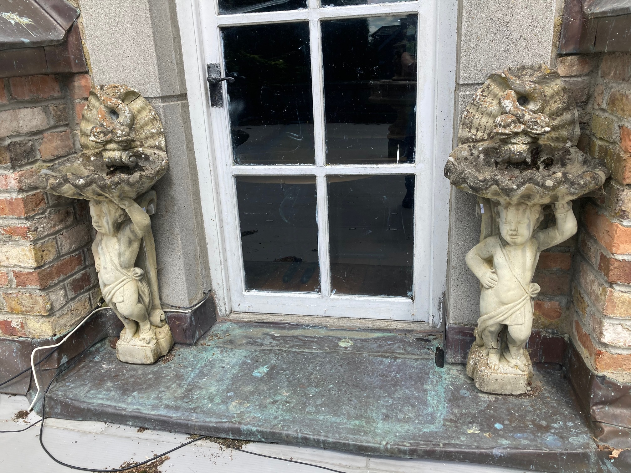 A pair of composition stone Garden Cherub Bird Baths, with shell bowls and double dolphin crests,