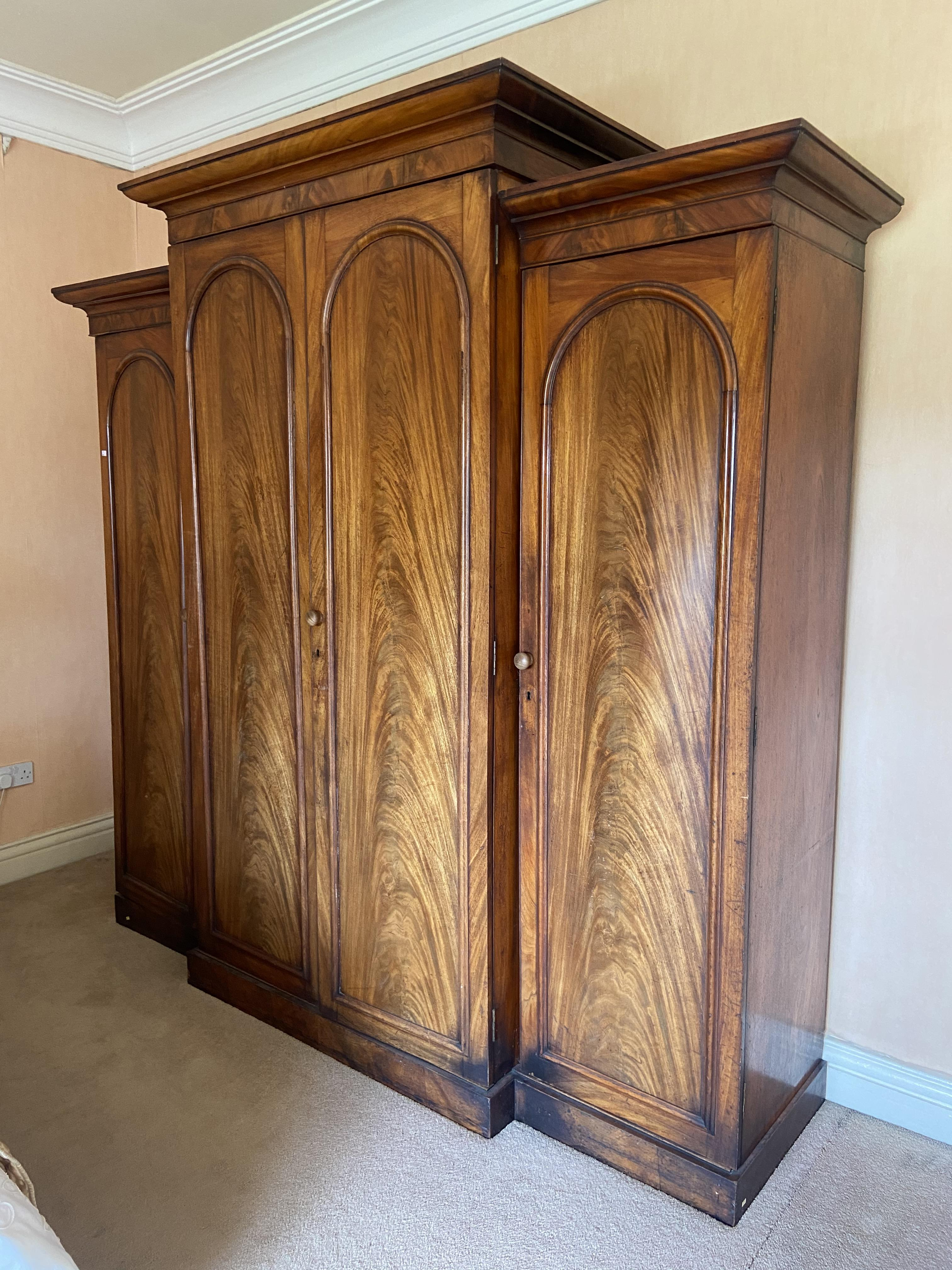 A fine Victorian breakfront Wardrobe, with raised centre and moulded cornice above four arched doors