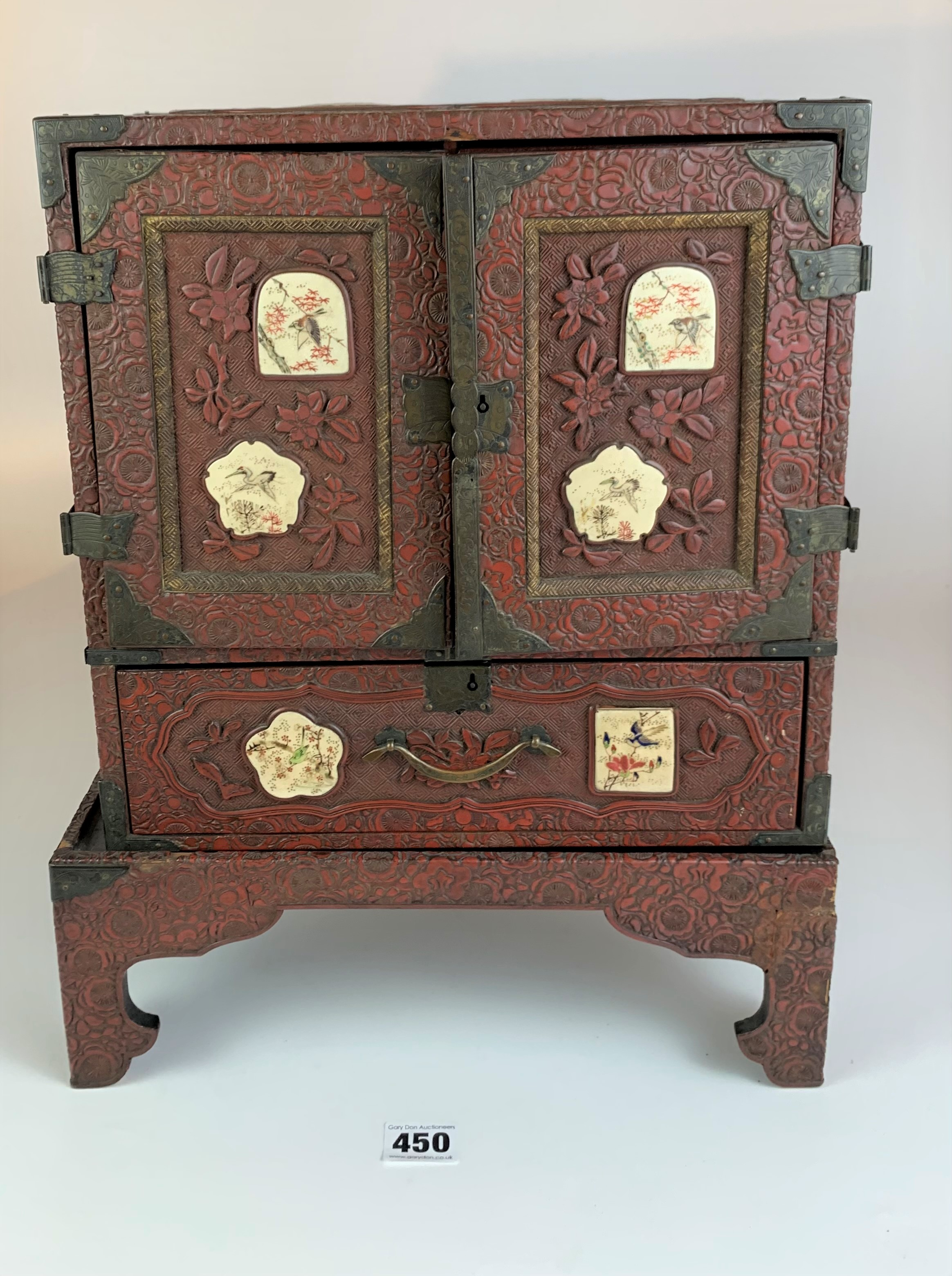 Small Japanese carved red cinnabar lacquer table cabinet with 8 Satsuma plaques on a matching stand.