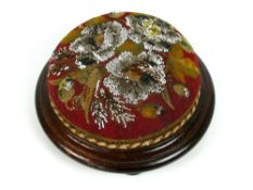 "Victorian mahogany and beaded tapestry footstool, on three bun feet, 11.5"" diameter (some losses"