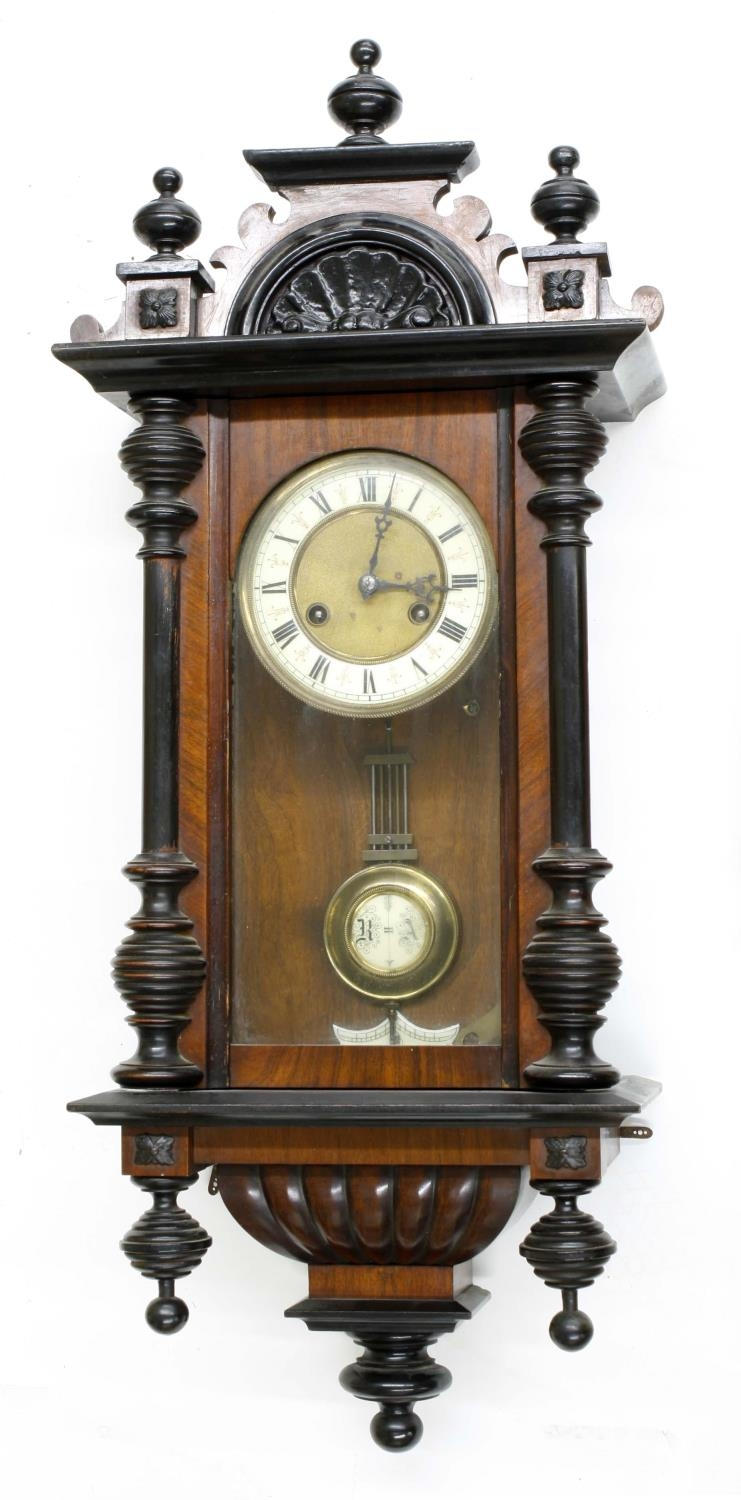 """Vienna walnut two-train wall clock, with ebonised pediment and pillared case, 31"""" high (pendulum and"""