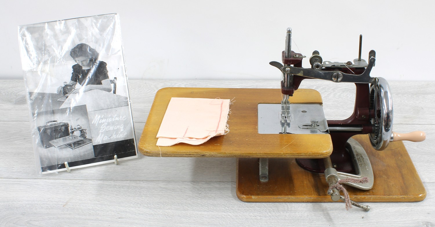 """Vintage Essex miniature sewing machine, with an instruction booklet and table clamp, 14"""" wide"""