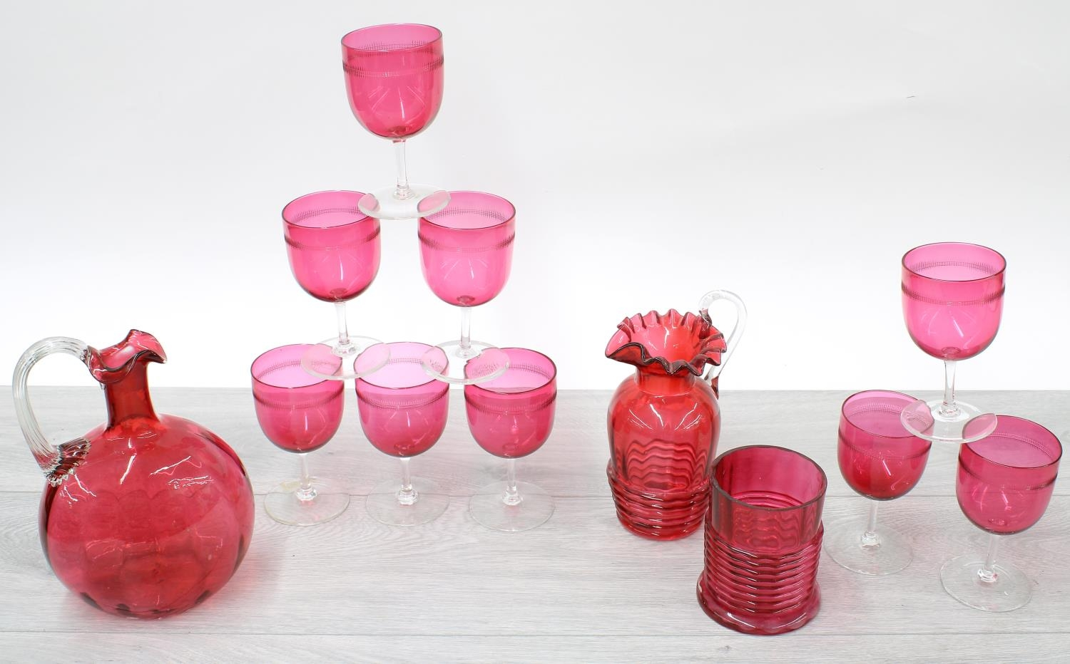 Set of nine Victorian cranberry wine glasses, cranberry glass decanter, jug and a cylindrical jar (