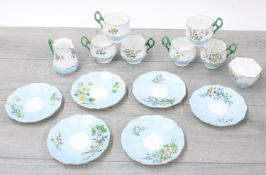 Attractive porcelainfluted tea service for six painted with flowers within pale blue borders,