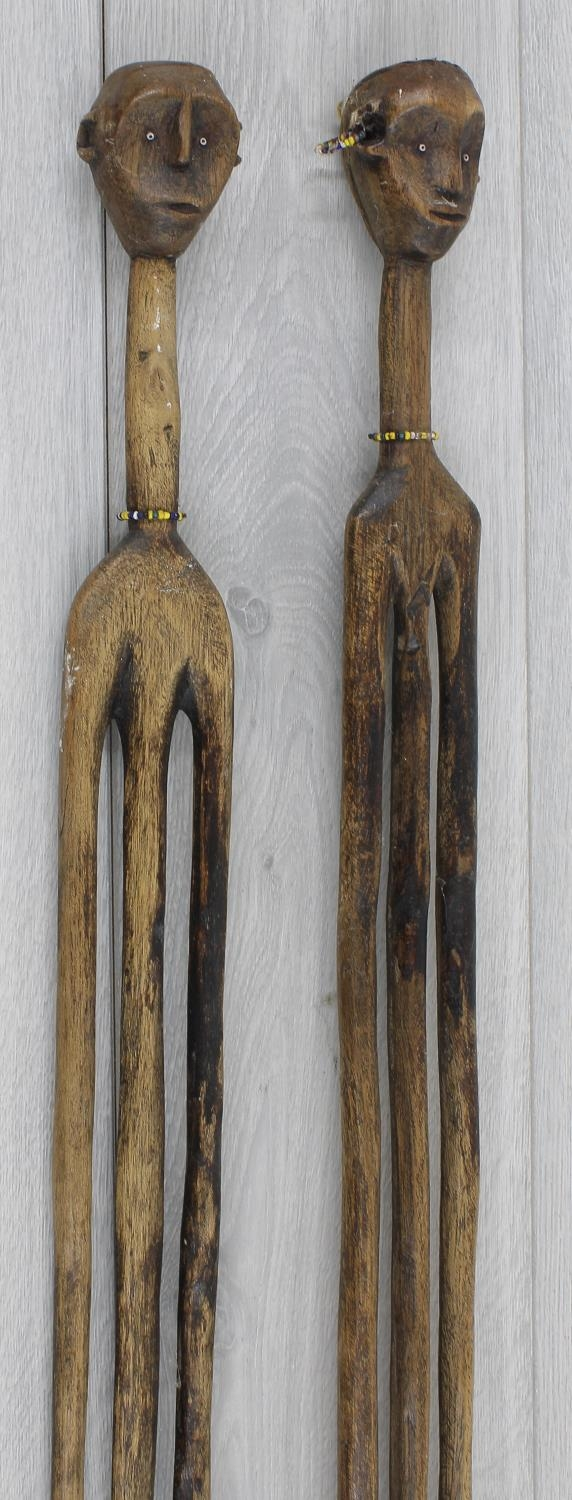 Two similar interesting African tribal wooden staffs, each surmounted with carved bead set heads,