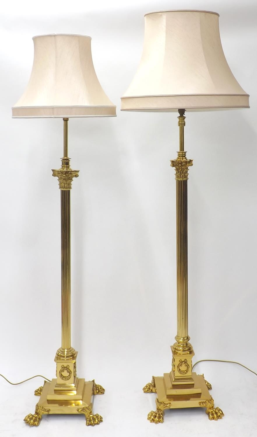 Matched pair of Corinthian column telescopic brass standard lamps with paw feet, with silk shades,