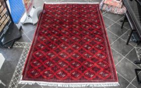 A Genuine Excellent Quality Persian Turkmen Carpet/Rug decorated in a Bukhari design on red ground.