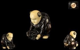 A Fine Quality Small Japanese Ivory and Carved Wood Netsuke Depicting a Small Boy Holding a Sack of