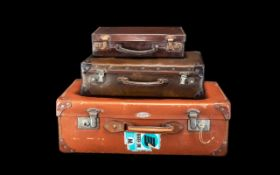 A Collection of Three Vintage Leather Suitcases comprising one tan case with Spartan plaque to
