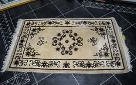 "Wool Rug, beige base with brown floral relief, fringed edges, measures 64"" x 36""."