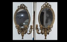 A Matching pair of Victorian Gilded Gesso Candelabra Mirrors of oval shape with a lace bow
