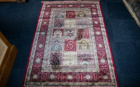 A Genuine Cashmere Red Ground Carpet/Rug. Persian panel design.As new condition. Measures 2.40 by 1.
