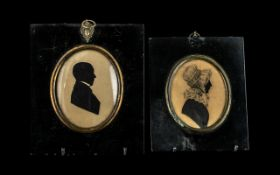 Two Antique Silhouettes in black period frames, one showing a lady in a bonnet, the other,