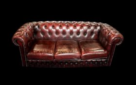 An Ox Blood Leather Chesterfield Sofa. With button back and arms. Measures approx 185 cms wide, 85