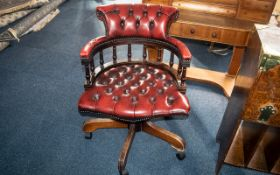 A Ox Wood Leather Captains Chair foot, backrest and seat of typical form. Legs are slightly loose.
