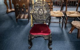 An Antique Profusely Carved Burmese Stand Chair, on shaped cabriole legs and a shaped round back,