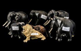 Group of Seven Ebony Elephants with tusks, plus a pottery lion figure (8)