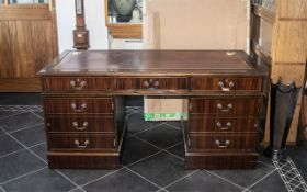 A Mahogany Effect Leather Topped Twin Pedestal Desk, with three frieze drawers,