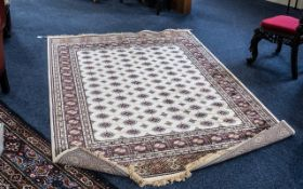 A Genuine Cashmere Rug, in as new condition, With cream ground, Measures 90 by 60 inches.
