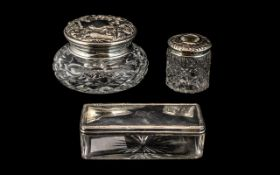 Three Silver Topped Glass Dressing Table Trinket Boxes, comprising a hair tidy,