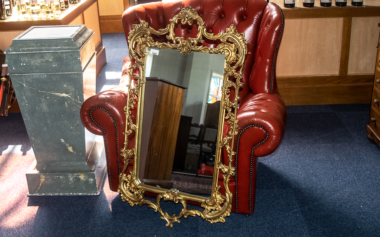 A Cast Gilded Metal Mirror in the Rococo Style, finely embellished with flowers and swaggering.
