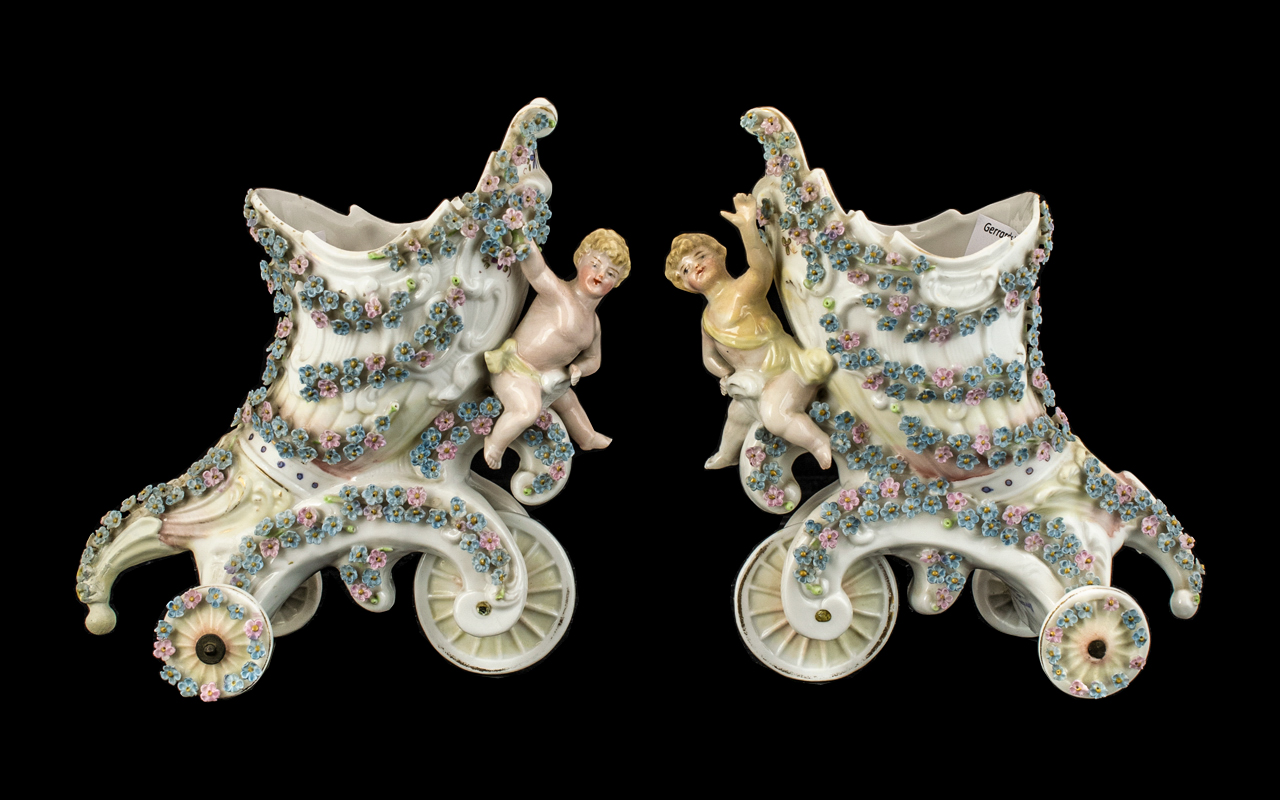 Pair of German Vases cornucopia shape on rolling wheels, with cherubs to front.