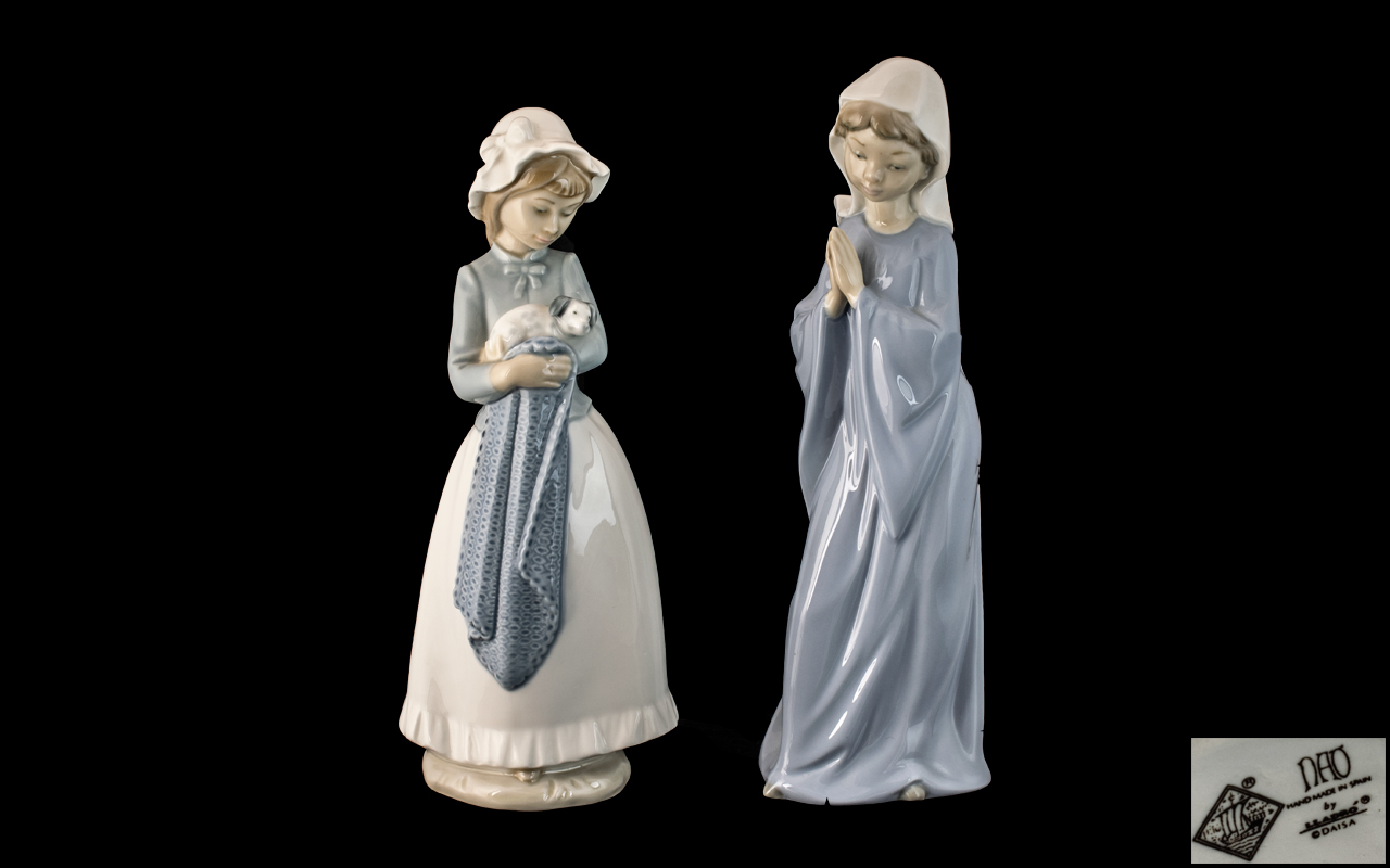Two Nao Figures, a girl holding a dog and a nun, praying, each 11 inches (27.