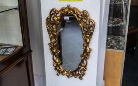 Ornate Gold Painted Mirror, oval shaped with scroll shapes and two winged figures,
