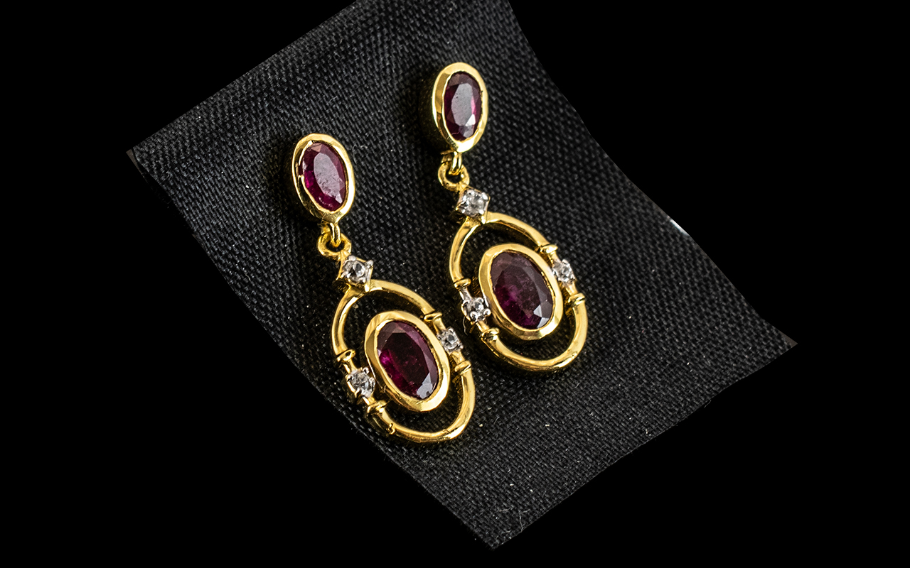 Ruby Drop Earrinngs, each earring comprising two oval cut rubies, of different sizes, the smaller,