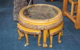 An Oriental Round Circular Nest of Tables of Circular Form, A Glass Top Above a Carved Fighting
