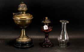 Two Oil Lamps, one on a decorative red and amber glass base,