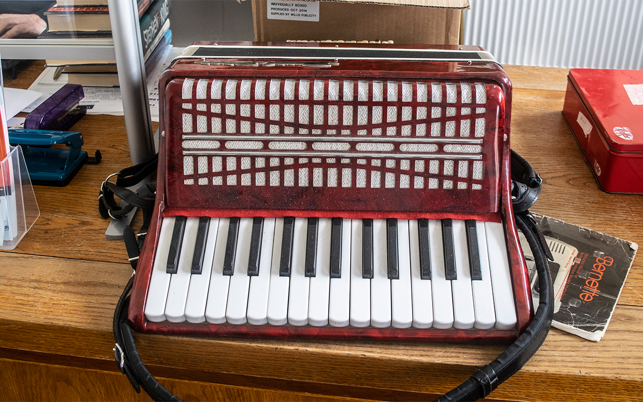 Accordion 'Pearl River' in red marble effect finish, with black trim and padded shoulder strap.