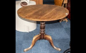 A George III Oak Tilt Top Table, circular top, raised on turned supports, cabriole legs.