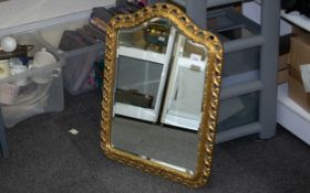 """Shaped Gilt Framed Mirror, with a bevelled edge, in the Florentine style. Measures 25"""" x 19""""."""