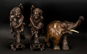 Two Carved Wooden Oriental Figures measuring 36 cm tall, together with a carved wooden elephant