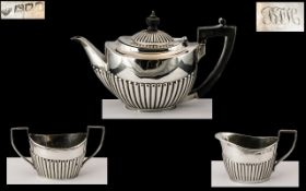 Small Silver Three Piece Harlequin Bachelor Tea Set, with embossed, fluted bodies and ebony handles;