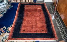 Hand Made Afghanistan Tribal Carpet with an inner blue border, on a burnt orange ground,