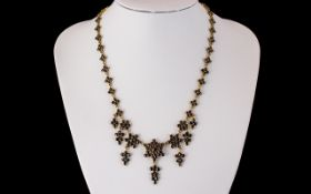 An Antique 19th Century Garnet Fringe Necklace, set in unmarked 9ct gold, of floral design with