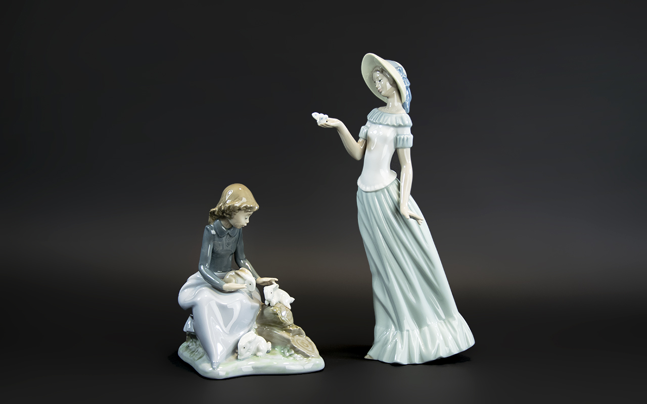 Two Nao Figures, comprising a 7'' tall figure of a seated girl with three rabbits; together with a